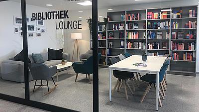 Stilvoll eingerichtete Bibliothek mit verschiedenen Sitz- und Arbeitsmöglichkeiten.