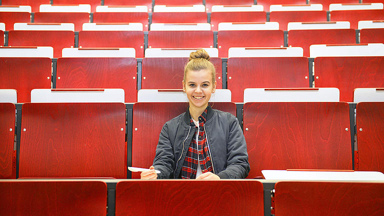 A female student sitting in a lecture hall.