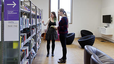 Zwei Frauen in einer Bibliothek.