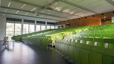 Blick in einen großen, leeren Hörsaal mit grünen Sitzreihen. Im Hintergrund ist eine Panoramaglasfront erkennbar, die den Blick ins Freie erlaubt.