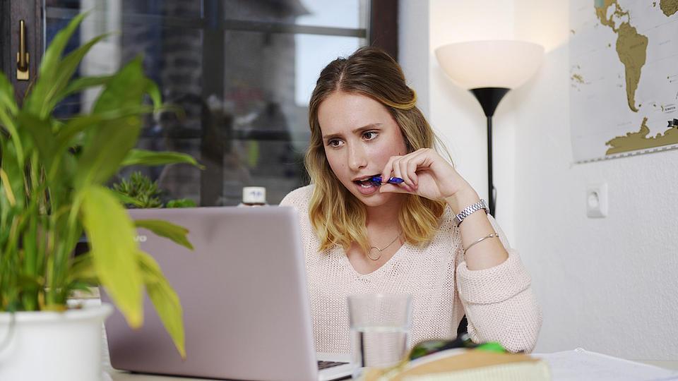 Eine junge Frau sitzt an einem Tisch, auf dem ein geöffneter Laptop steht und schaut auf diesen.