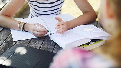 Zwei Frauen sitzen an einer Bank und bereiten sich mit Büchern auf eine Prüfung vor