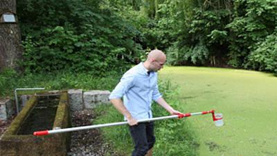 Ein Student entnimmt eine Wasserprobe aus dem See