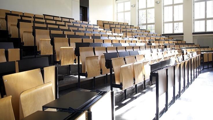 In einem Hörsaal sind sieben Sitzreihen mit Panoramablick angeordnet. Im Hintergrund sind sehr große Fenster zu sehen.