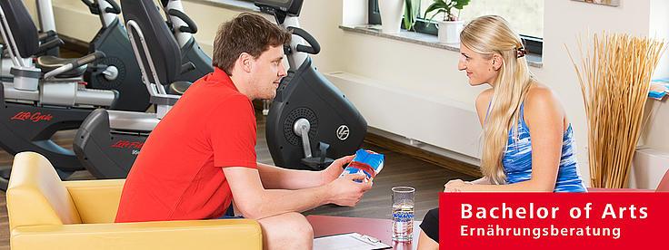 Zwei Studierende unterhalten sich im Fitnessstudio.