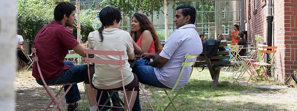Mehrere Studierende sitzen auf dem Campus zusammen.