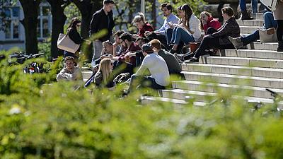 Studierende sitzend auf den Treppen des Campus in Würzburg