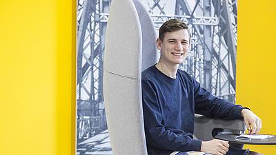 Ein junger Mann sitzt auf einem gelben Stuhl.