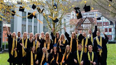 Studierende mit Roben werfen Hüte in die Luft.