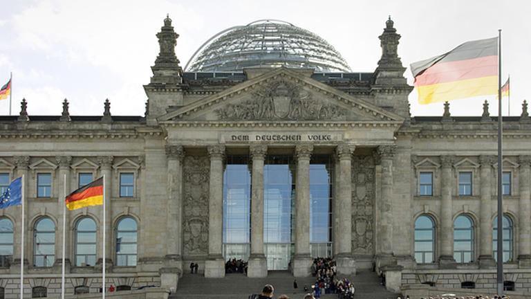 Aufnahme des Reichstagsgebäudes mit Glaskuppel in Berlin. Auf und vor dem Gebäude stehen mehrere Deuschlandflaggen und eine Europaflagge.