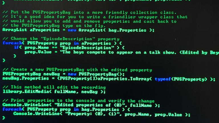 Aufnahme von einem schwarzen Bildschirmhintergrund auf dem ein Programmiercode in leuchtendem grün und blau dargestellt ist.