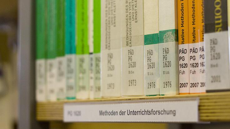Nahaufnahme eines Bücherregalteils in einer Bibliothek. Im Regal stehen mehrere verschiedene Bücher, die der Kategorie