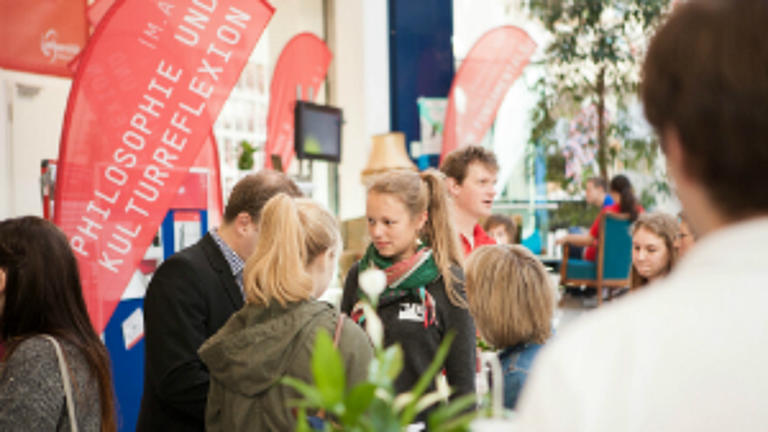 Viele junge Menschen auf einer Infomesse.