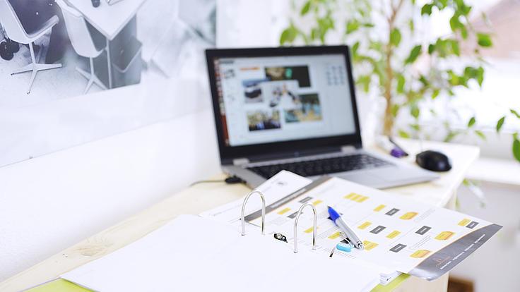Laptop und Arbeitsmaterialien auf einem Schreibtisch.