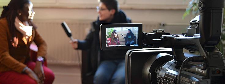Eine Fernsehkamera filmt ein Interview.