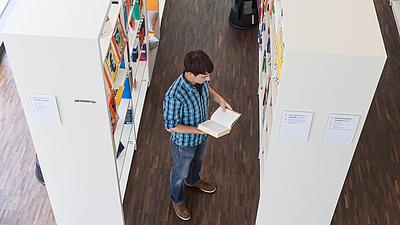 Ein Studierender steht in einer Bibliothek.