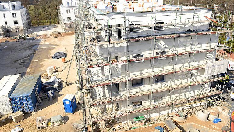 Ein eingerüstetes neu erbautes vierstöckiges Mehrfamilienhaus auf einem Baustellengelände aufgenommen aus der Vogelperspektive.