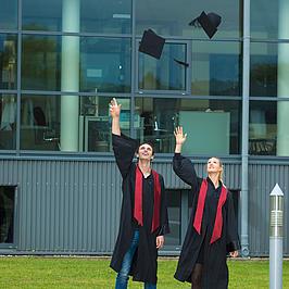 Zwei Studierende werfen Doktorhüte in die Luft.