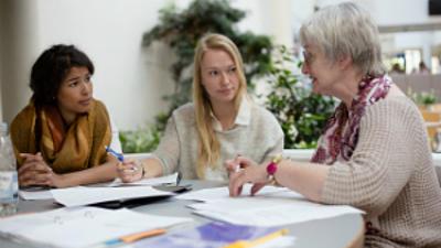 Studentinnen und eine Dozentin in einem Seminar.