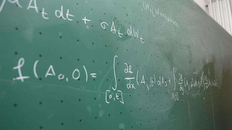 Eine mit Mathe-Gleichungen beschriebene Tafel.