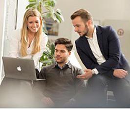 Drei Studierende schauen in einen Laptop.