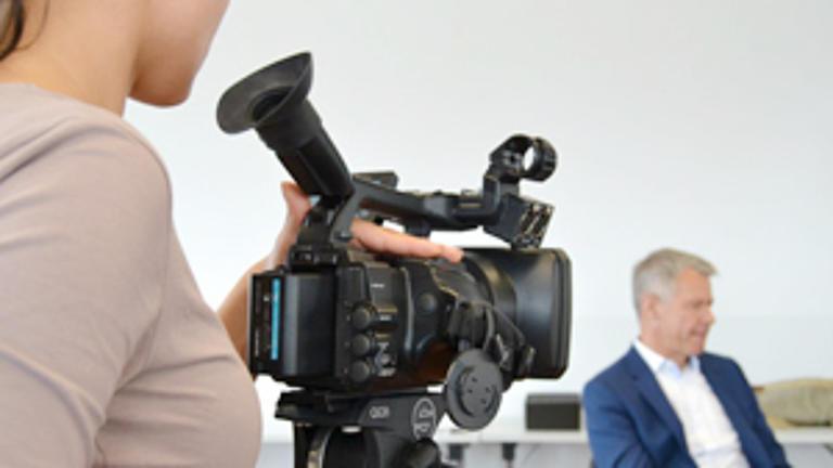 Eine Studentin filmt mit einer Kamera ein Interview.