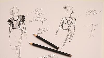 Zwei handgezeichnete Modeentwürfe liegen aufgefächert auf einer weißen Fläche, darauf liegen zwei schwarze Zeichenstifte.