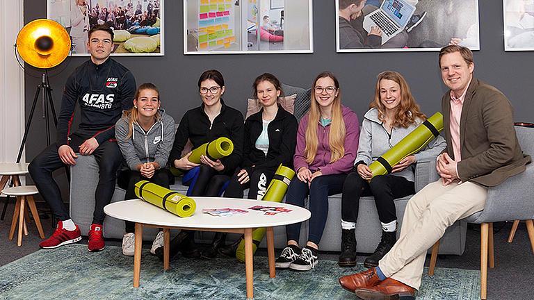 Sportlich gekleidete Studierende sitzen neben einer älteren Person auf einer Couch, in ihren Händen halten sie eingerollte Sportmatten.