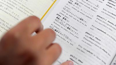 Nachaufnahme eines geöffneten japanisch-deutschen Wörterbuches, auf dessen Seite eine Hand ein Lesezeichen hält.
