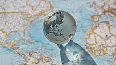 Detailaufnahme von einer Glasweltkugel auf einer Landkarte.