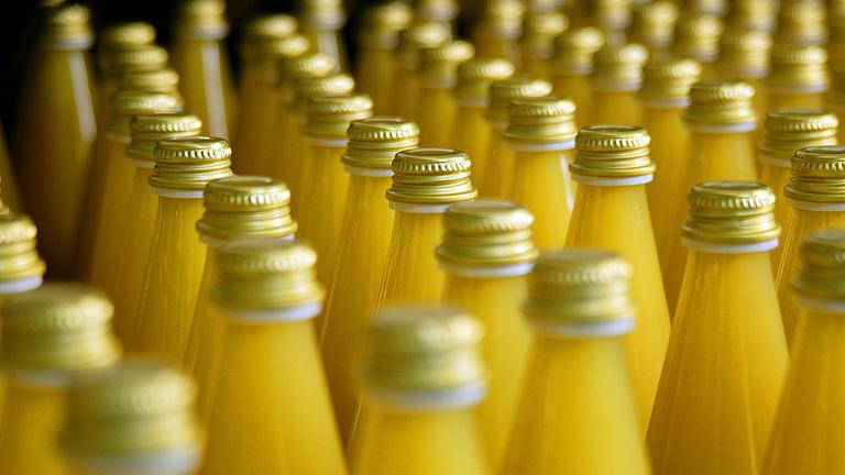 Detailaufnahme von frisch befüllten Orangensaftflaschen in der Produktion. Man blickt über die Glasflaschen mit Metalldeckeln.