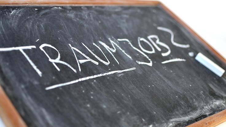 """Auf einer schräg liegenden Schreibtafel mit Holzrand steht in Großbuchstaben das Wort """"Traumjob"""""""