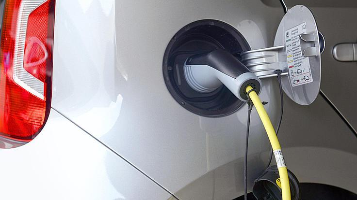 Ein Elektro-Auto ist mit einem Ladekabel verbunden.