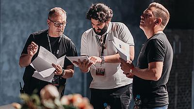 Drei Dozenten bei der Auswahl von Arbeitsblättern