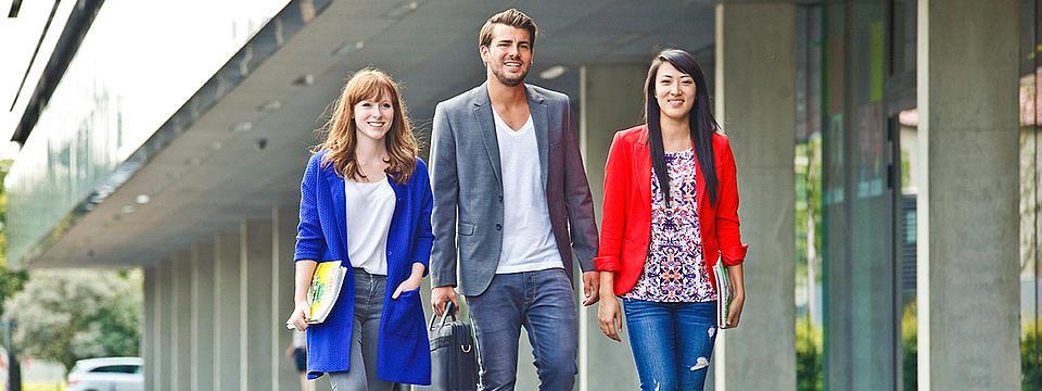 Drei Studierende laufen über den Campus.