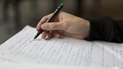 Männliche Hand schreibt mit einem Stift auf ein beschriebenes Blatt Papier