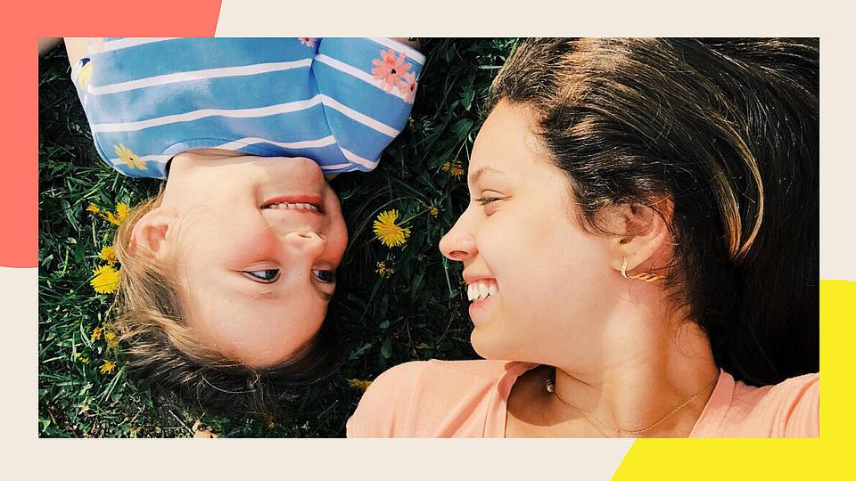 Eine Frau mit Kind liegend auf einer Wiese