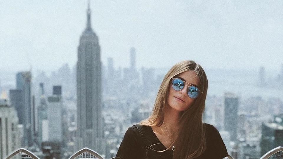 Eine Studentin in New York. Im Hintergrund das Empire State Building