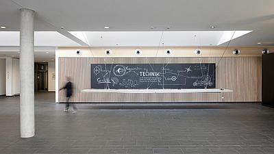 In einem hellen Foyer mit Säule und dunklen Bodenfliesen hängt unter einem großen Lichtschacht ein langes flaches Objekt,
