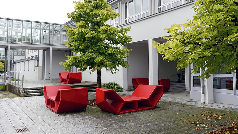 Zu sehen ist ein modernes Hochschulgebäude mit roten Sitzbänken davor.