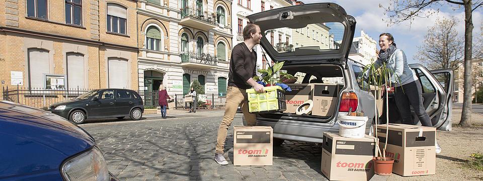 Zwei Menschen packen Umzugskartons aus einem Auto aus.