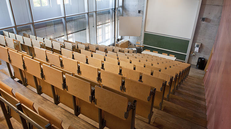 Blick von oben, aus den Sitzreihen, auf einen leeren Vorlesungssaal.