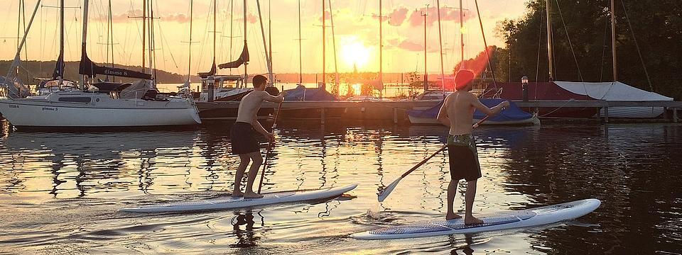 Zwei Männer paddeln auf Surfbrettern.