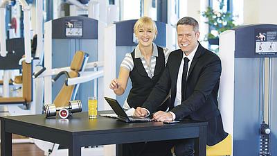 Zwei Menschen in Business-Klamotten stehen in einem Fitnessstudio.