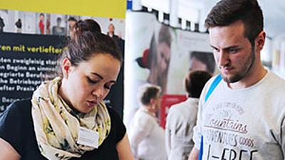 Zwei Studierende bei einer Info-Messe.