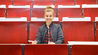 Eine Studentin sitzt in einem Hörsaal.