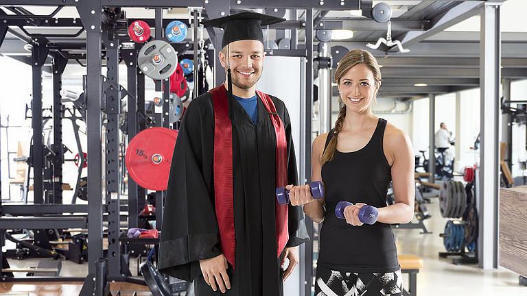 Zwei Menschen stehen in einem Fitnessstudio. Die Frau trägt Sportklamotten, der Mann eine Robe und einen Doktorhut.