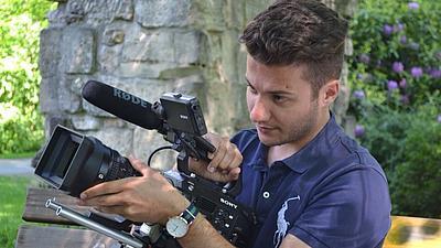 Julian Dagistan hält eine Filmkamera