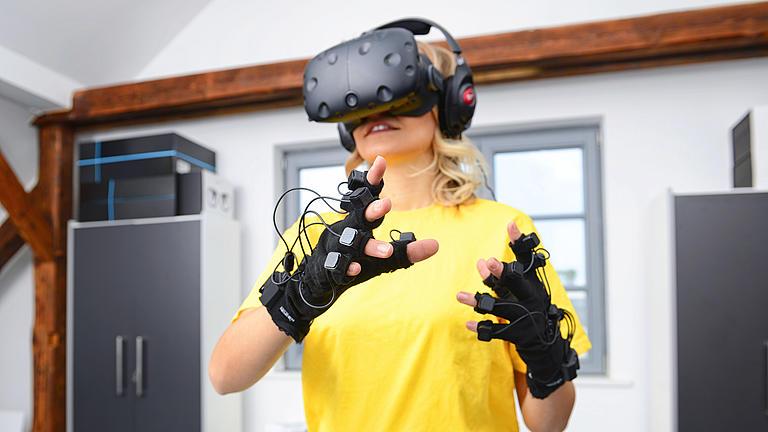 Frau steht mit einer Virtual Reality Brille in einem Raum und testet deren Funktionen