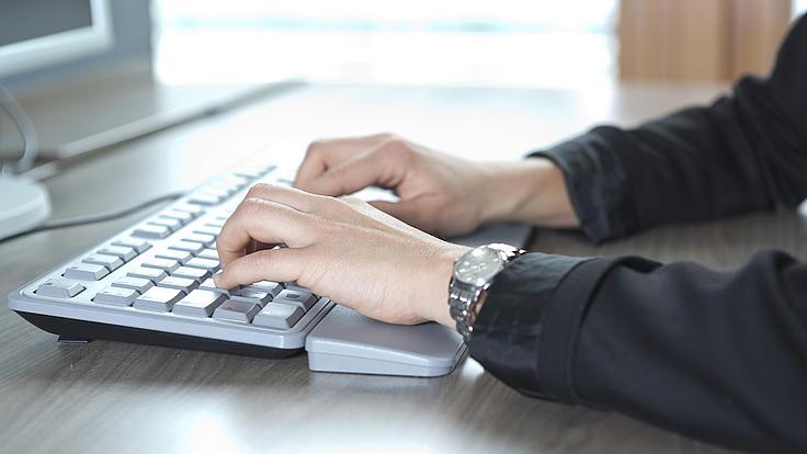 Zwei Hände einer Person schreiben auf einer silbernen Tastatur, die auf einem Tisch vor einem Monitor steht.